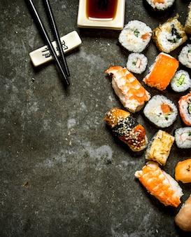 Суши-роллы с морепродуктами и соевым соусом. на каменном столе.