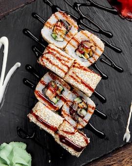 Суши роллы с кунжутом подаются с соусом и васаби