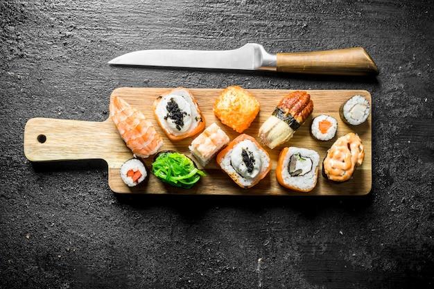 黒の素朴なテーブルの上にナイフでまな板の上にエビ、野菜、サーモンと巻き寿司