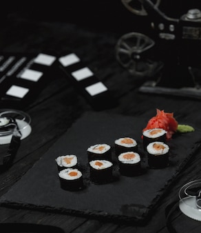 Sushi rolls with smoked salmon on dark table.