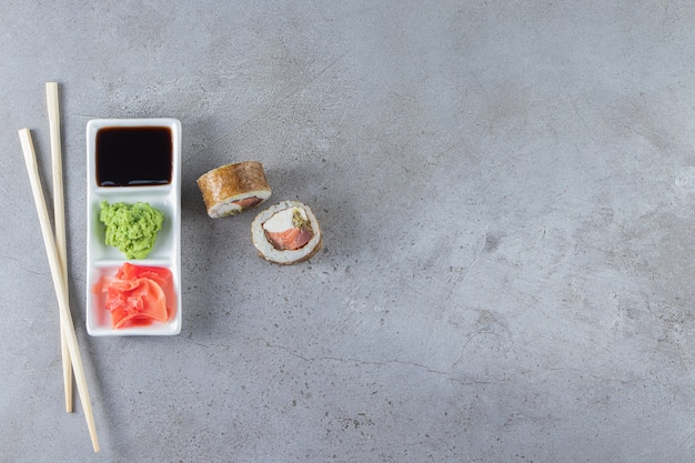 Sushi rolls with soy sauce placed on a white board with chopsticks .