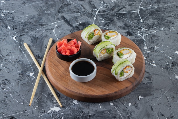 Sushi rolls with soy sauce placed on a wooden board .