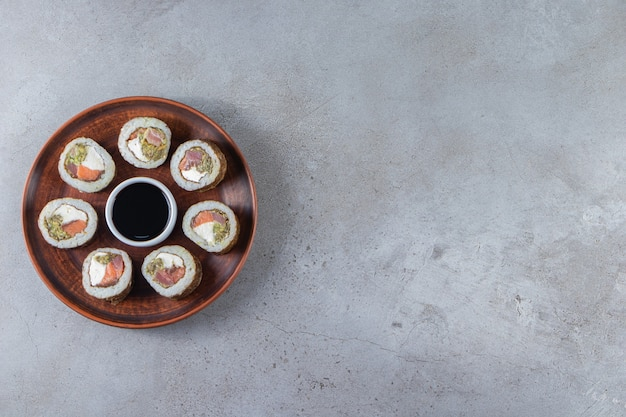 Sushi rolls with soy sauce placed on a wooden plate .