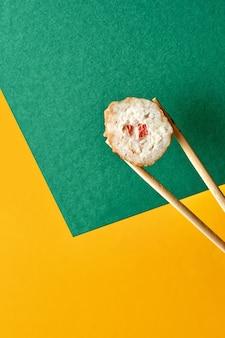 Суши-роллы с палочками. желтый и зеленый фон. креативная концепция.