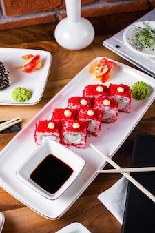 Суши роллы с икрой тобико подаются с соевым соусом, имбирем и васаби