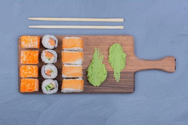 Суши-роллы с соусом васаби на деревянном блюде