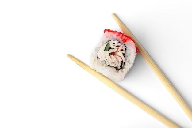 흰색 배경에 분리된 젓가락에 흰살 생선, 오이, 토비코 캐비어를 넣은 스시 롤.