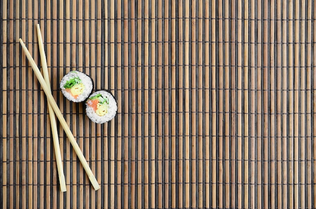Sushi rolls and wooden chopsticks lie on a bamboo straw serwing mat.