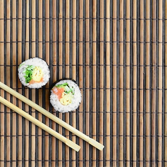 Sushi rolls and wooden chopsticks lie on a bamboo straw serwing mat