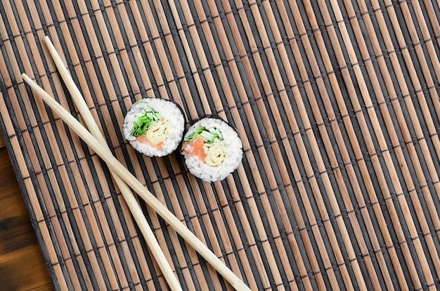 Sushi rolls and wooden chopsticks lie on a bamboo straw serwing mat.