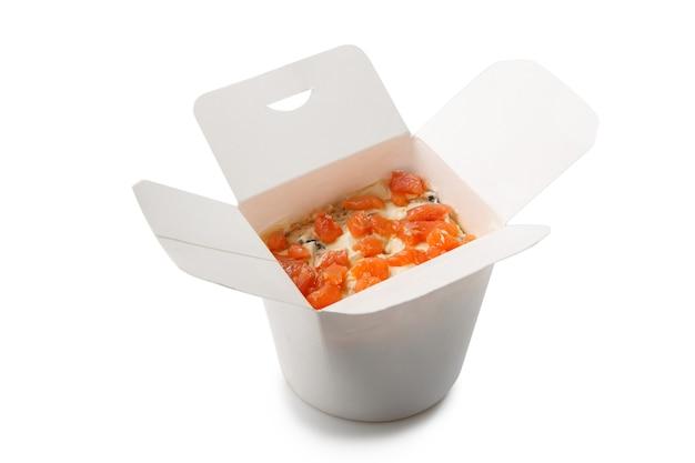Салат суши в картонной коробке на вынос. вид сверху. все ингредиенты укладываются слоями. покрыта на белом.