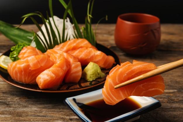 白いお皿に鮭とマグロのエビとわさび。木のテーブルの上