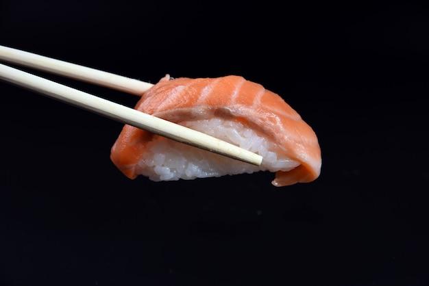 Sushi salmon nigiri in chopsticks over black
