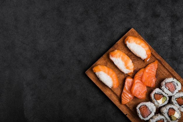 Sushi and salmon slices on wooden chopping board over the black backdrop