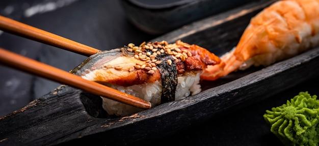 Суши-сашими с креветками и соевым соусом, подается с деревянными палочками и васаби на черном столе ...