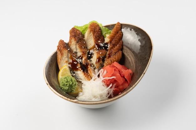 Sushi sashimi unagi. eel slices in teriyaki sauce with daikon radish, ginger, wasabi, lettuce and lemon wedge on a pad of rice