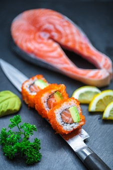 Sushi served on japanese knife on a black slate plate