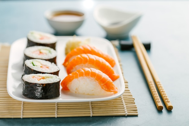 Sushi served on plate on blue table