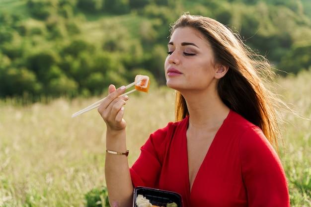 緑の丘の上の寿司セットと女の子。