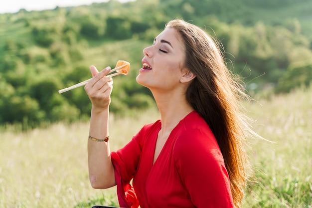 초밥 세트와 푸른 언덕에서 초밥을 물기 위해 손을 뻗는 소녀.