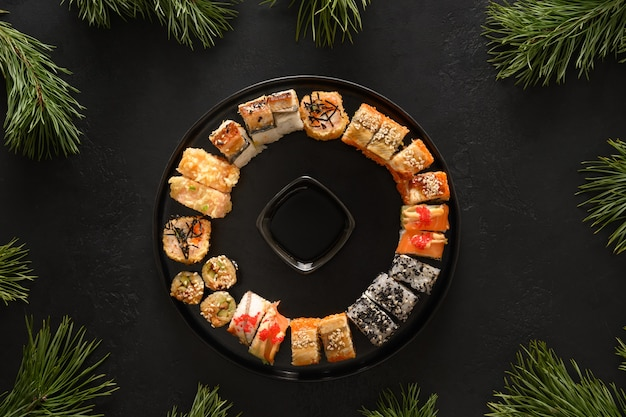 Sushi set as christmas wreath decorated fir tree branches on black background. view from above. copy space. delivery food.