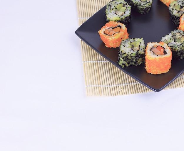 寿司セット-黒いプレートにさまざまな種類の巻き寿司と箸