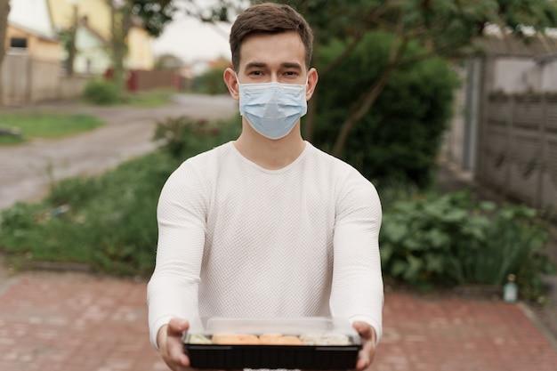 Суши-набор в коробке онлайн-сервис доставки здоровой еды на машине. курьер красивый мужчина в медицинской маске дает вам суши-коробку. японская кухня.