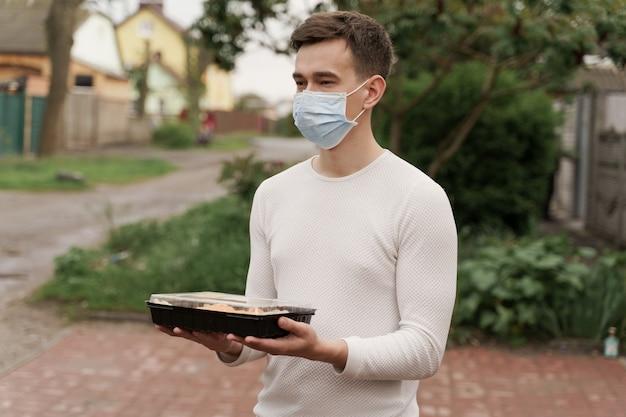 Суши-набор в коробке онлайн-сервис доставки здоровой еды на машине. курьер человек в медицинской маске с коробкой суши стоит перед автомобилем.