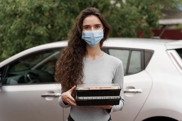 스시는 자동차로 건강한 음식 배달 서비스를 제공합니다. 2 초밥 상자와 의료 마스크에 매력적인 여자는 차 앞에 서있다.
