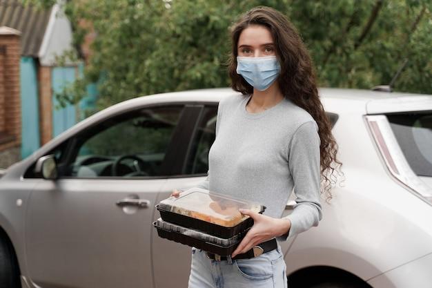 스시는 자동차로 건강한 음식 배달 서비스를 제공합니다. 2 초밥 상자와 의료 마스크에 소녀 택배는 차 앞에 서 있습니다.