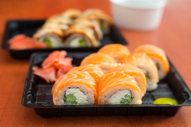 鮭、海老、わさび、生姜が入ったプラスチックの箱に入った寿司。伝統的な日本料理。デリバリーフードサービスのコンセプト。