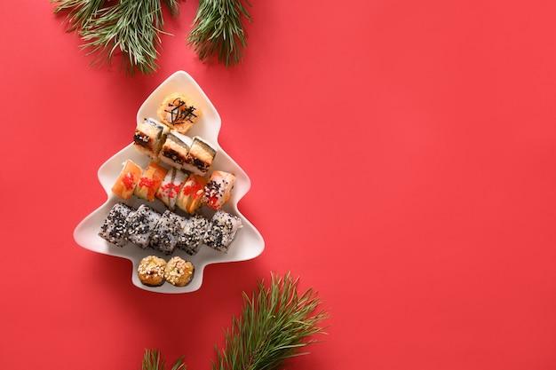 Суши в тарелке, как рождественская елка, украшенная еловыми ветками на красном фоне. вид сверху. место для текста. стиль flatlay.