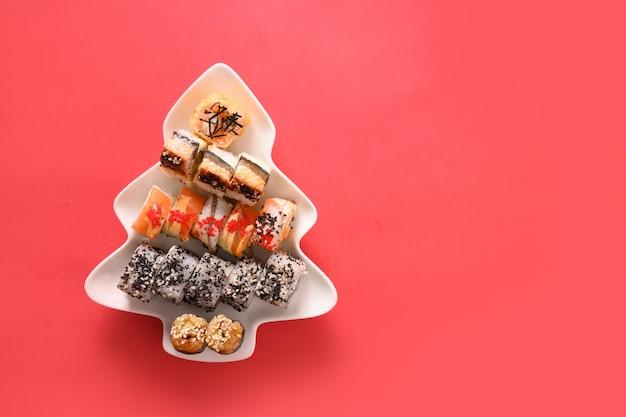 Суши в тарелке, как рождественская елка, украшенная еловыми ветками на красном