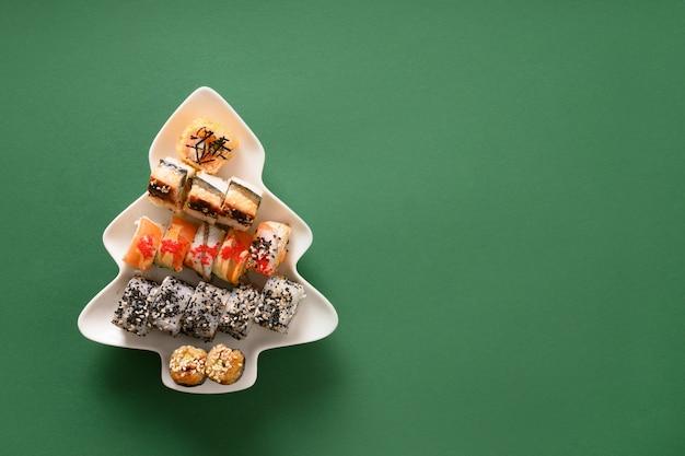 초밥 접시에 크리스마스 트리 장식 녹색 배경으로 설정합니다. 위에서 봅니다. 텍스트를위한 공간. flatlay 스타일.