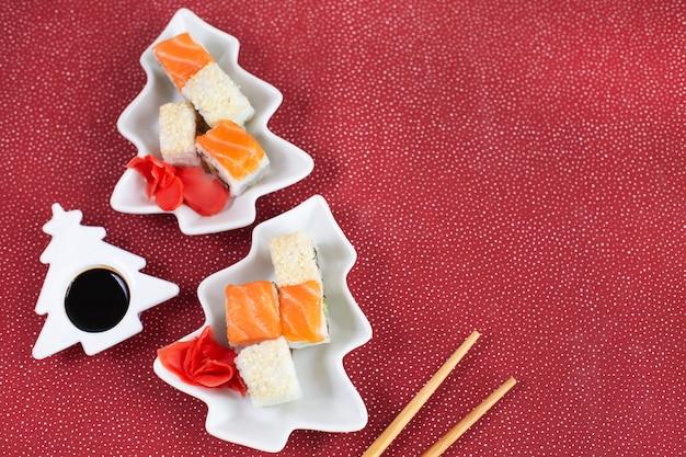 Суши в тарелке как новогодняя елка на праздничном фоне