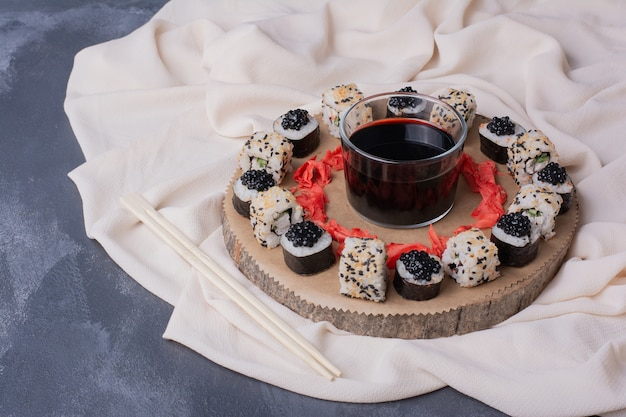 Sushi set. maki and alaska sushi rolls on wooden plate with tablecloth,pickled ginger and soy sauce.