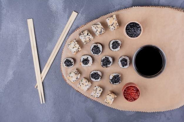 寿司セット。巻き寿司とアラスカ巻き寿司は、箸、キャビア、醤油で木の板に巻かれます。