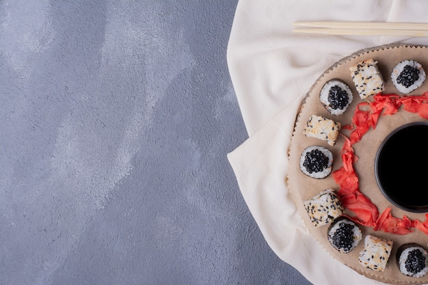 寿司セット。巻き寿司とアラスカの寿司は、テーブルクロス、生姜のピクルス、醤油を添えて木の板に巻かれています。