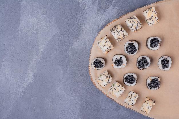 寿司セット。木の板に巻き寿司とアラスカ巻き寿司。