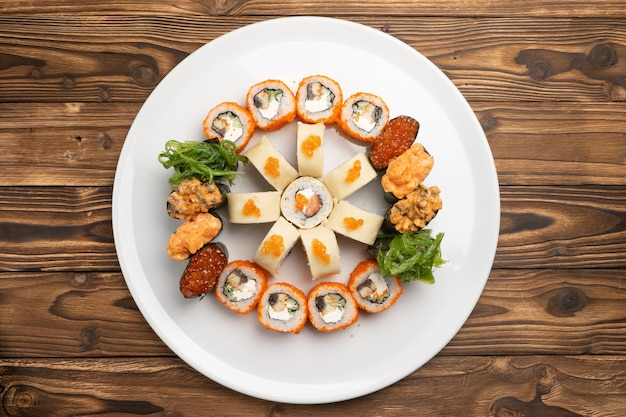 Sushi set of maki rolls with salmon and eel and gunkans with caviar and chuka salad on a white round ceramic plate