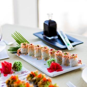 Суши-сет нигири и суши-роллы с соусом на белой тарелке на столе в ресторане