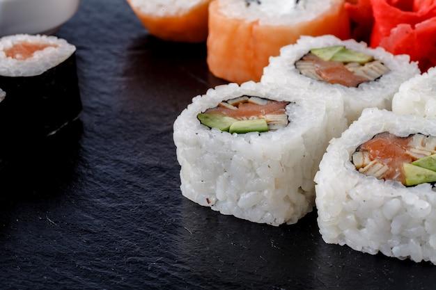 Sushi set nigiri, sushi rolls and sashimi served on stone slate