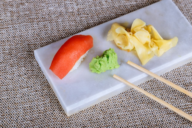 Sushi set nigiri and sushi rolls on wooden serving board over stone texture background.