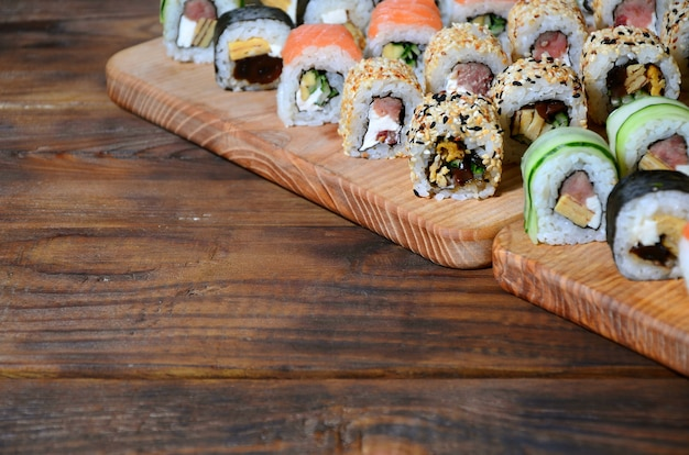 Sushi set of a number of rolls is located on a wooden cutting board on a table in the kitchen of a sushi bar.