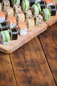 Sushi set of a number of rolls is located on a wooden cutting board on a table in the kitchen of a sushi bar