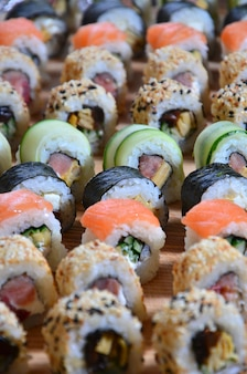 Sushi set of a number of rolls is located on a wooden cutting board