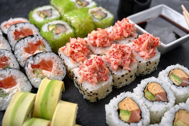 Суши-сет из разных роллов, с икрой летучей рыбы, тобико, креветками, угрем, лососем, авокадо, палочками и соевым соусом