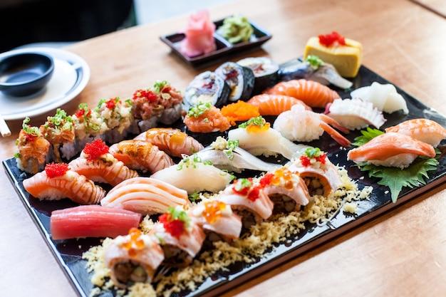 Суши, установленные на черной тарелке японская еда в ресторане