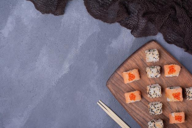 Набор суши. роллы филадельфии и аляски на деревянной тарелке с палочками для еды.