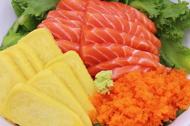 Суши набор сырой лосось сашими, яйцо тобико с овощами.